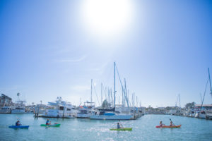 A group of kayaks paddles past boats moored in Channel Islands Harbor